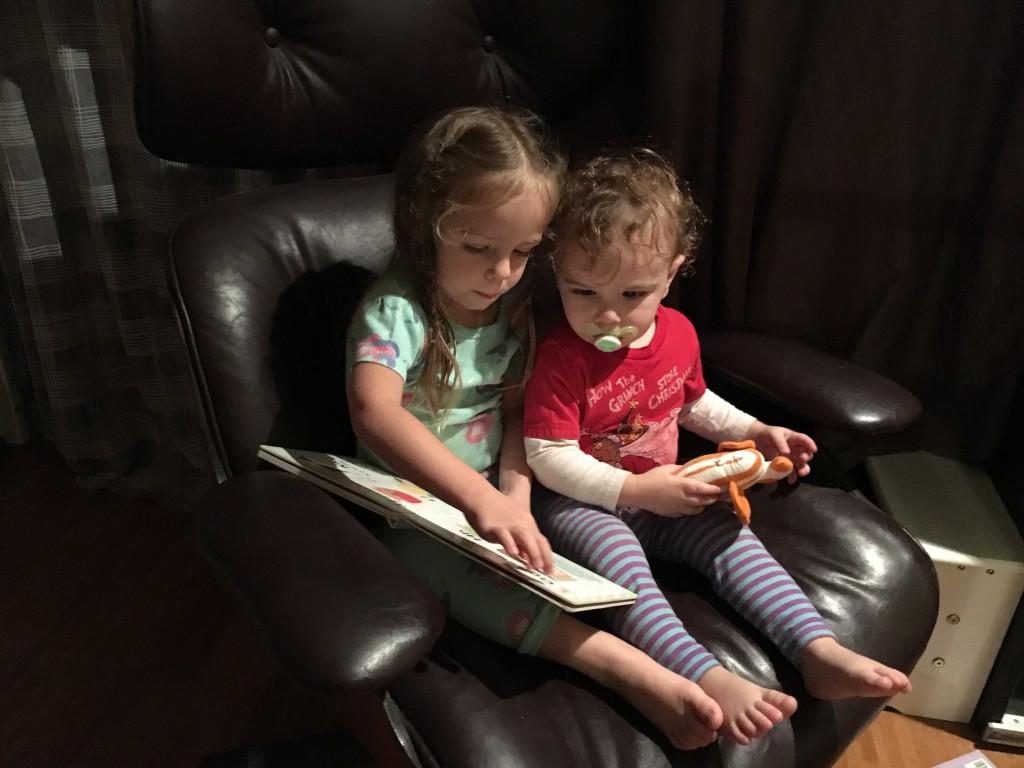 Sister reading to little bro before bedtime.